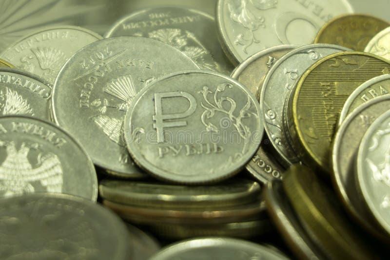 小在一个巨大数目的金属俄国金钱在白色背景 库存图片