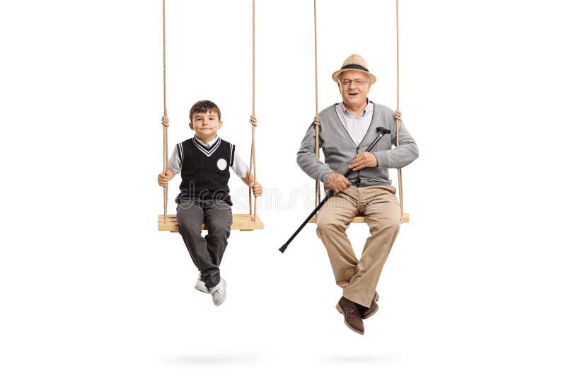 小在摇摆安装的男小学生和一个成熟人 免版税库存照片