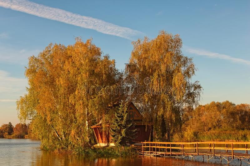 小在湖中间的海岛和树美丽如画的风景有被放弃的房子的 秋天早晨风景 免版税图库摄影