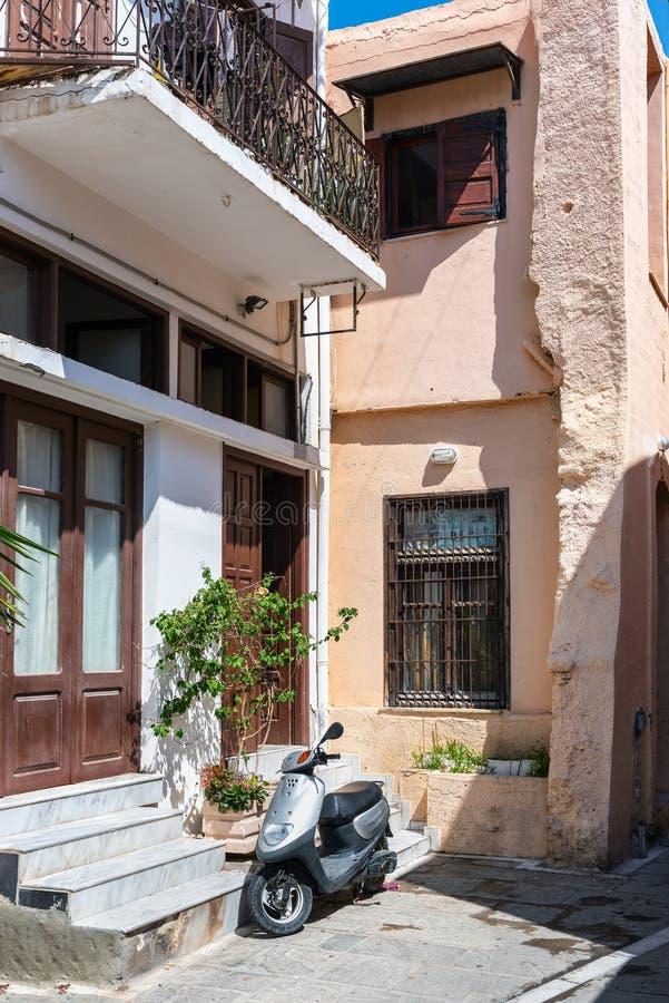 小型摩托车在罗希姆诺镇,克利特海岛,希腊停留停放在老希腊房子附近门面  免版税库存图片