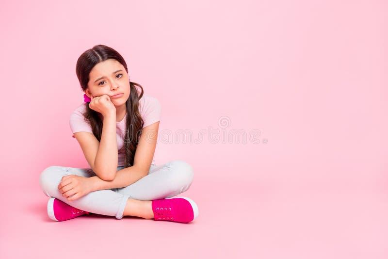 小夫人大型照片坐地板前类在假期前穿戴偶然成套装备桃红色的乏味演讲 免版税库存照片