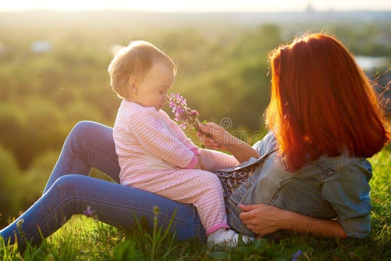小女儿嗅到的花坐妈妈,说谎在草,当日落时 库存图片