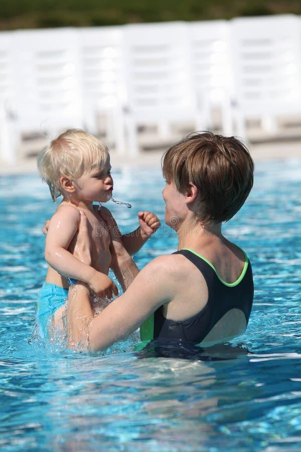 小女儿母亲池游泳 免版税图库摄影