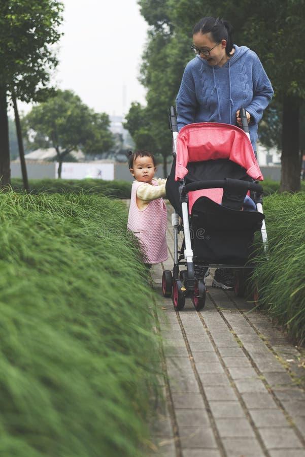 小女儿设法推挤婴孩carseat 免版税图库摄影