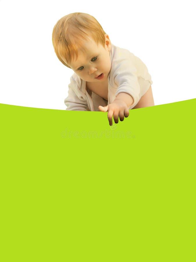 小女婴婴孩好奇地弯曲在色的板料 免版税库存照片