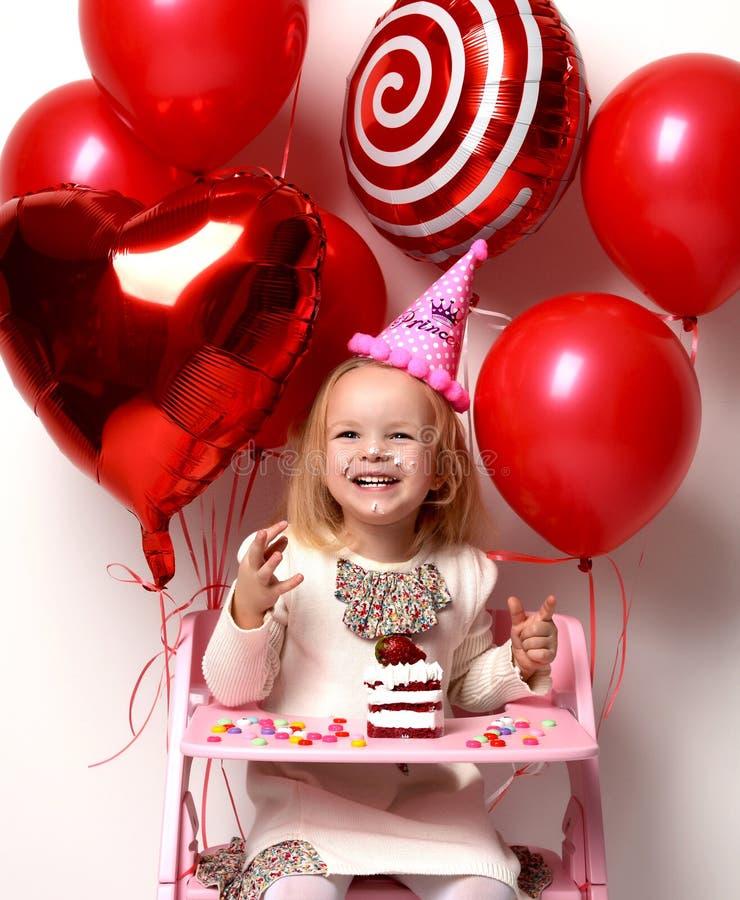 小女婴孩子庆祝与甜蛋糕和糖果的生日 免版税库存照片