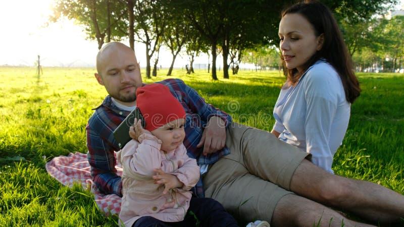 小女婴采取智能手机并且回答电话和谈话关闭  有愉快的家庭一基于一个夏天 免版税库存照片