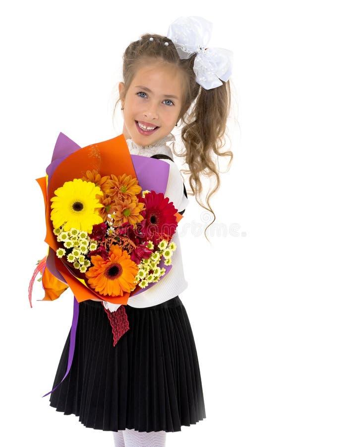 小女孩上有花花束的学  免版税库存照片