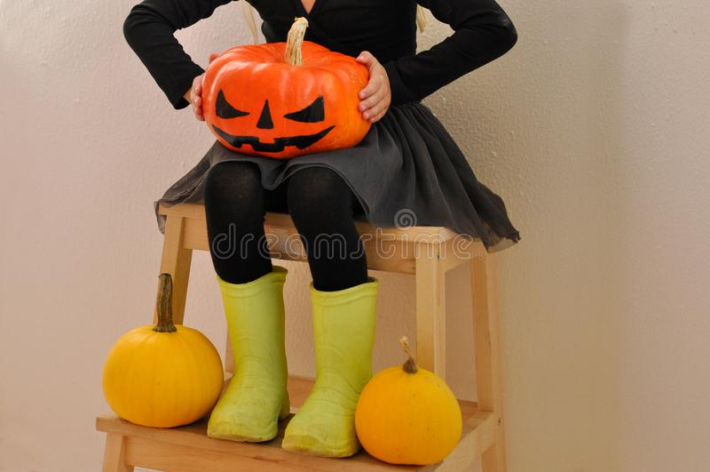小女孩为万圣夜拿着一个可怕南瓜,坐其他南瓜围拢的长凳 Closup 图库摄影