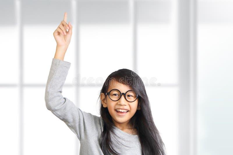 小女孩举她的手和指向手指  免版税库存照片
