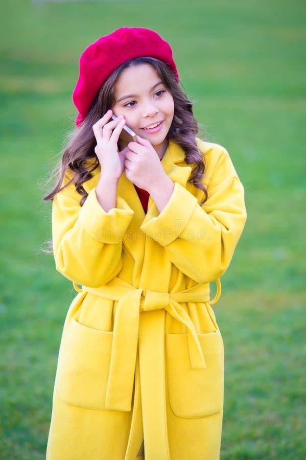 小女孩举行智能手机或手机 现代一代通信 移动通信概念 孩子 库存照片