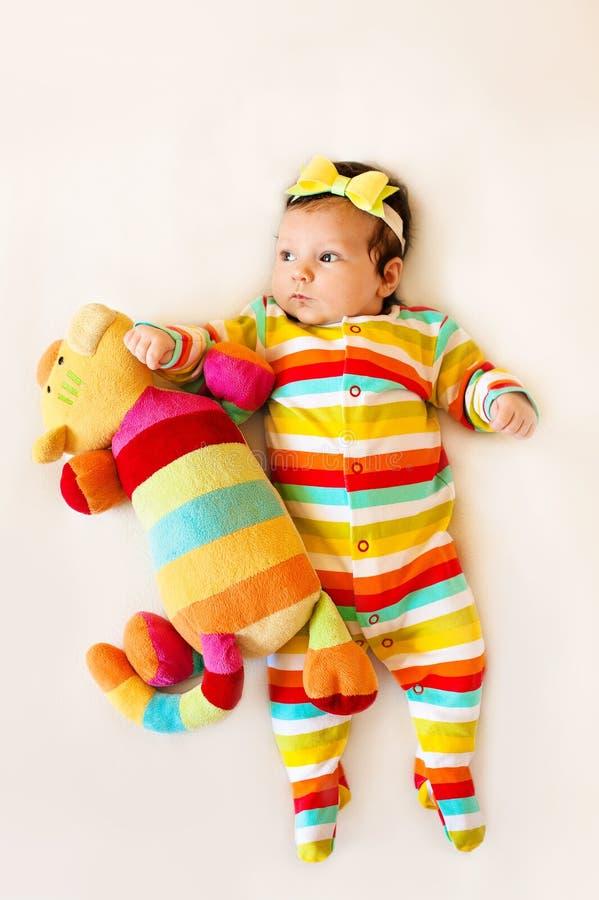 小女孩五颜六色的睡衣的和有在顶头谎言白色一揽子玩具的一把弓的镶边了猫 图库摄影