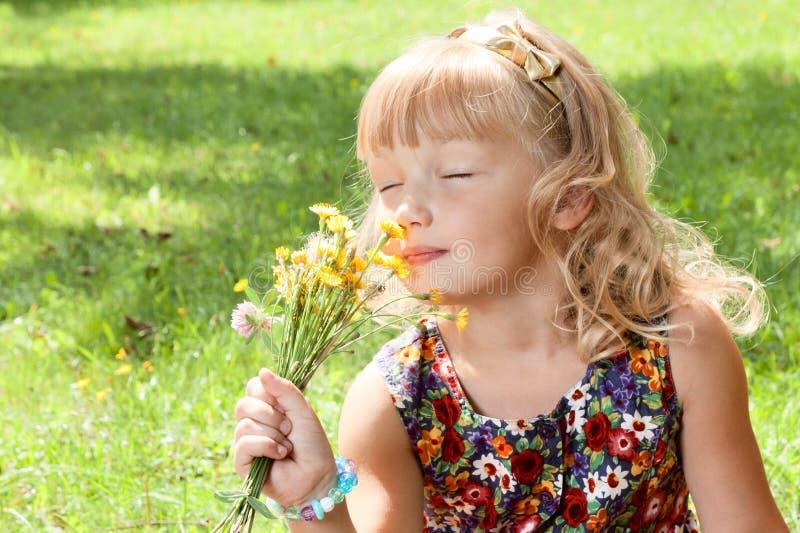 小女孩享用花的气味 库存照片