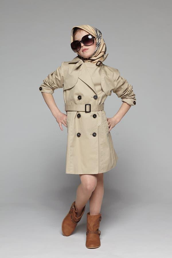 塑造小女孩佩带的军用防水短大衣和太阳镜 图库摄影
