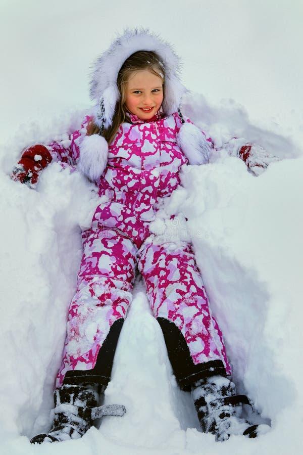 小女孩佩带的冬天在雪给说谎穿衣 库存照片