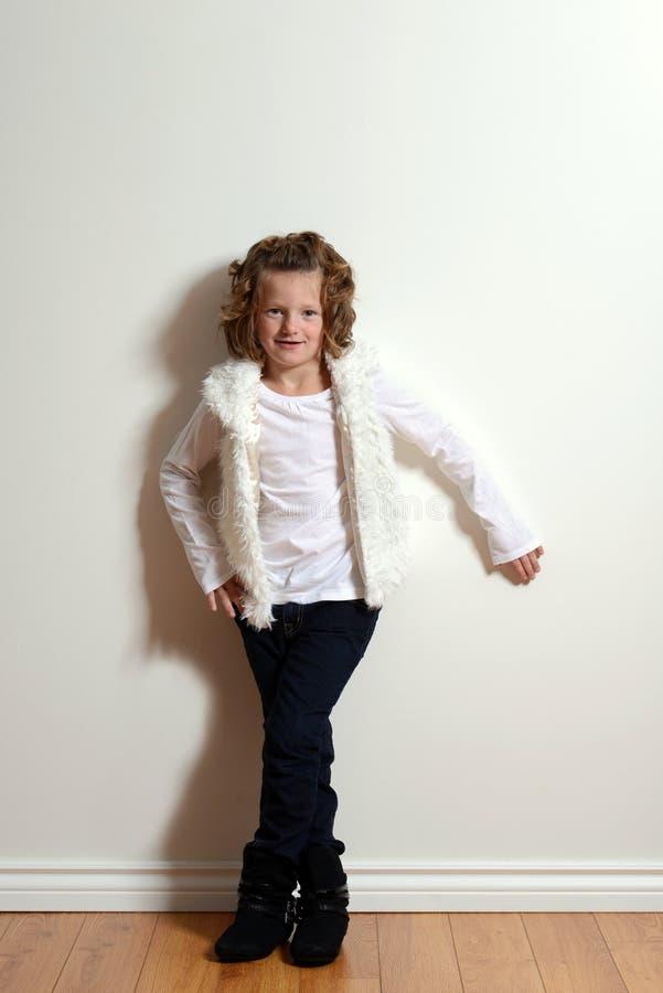 小女孩佩带的牛仔裤和毛皮背心 免版税库存图片