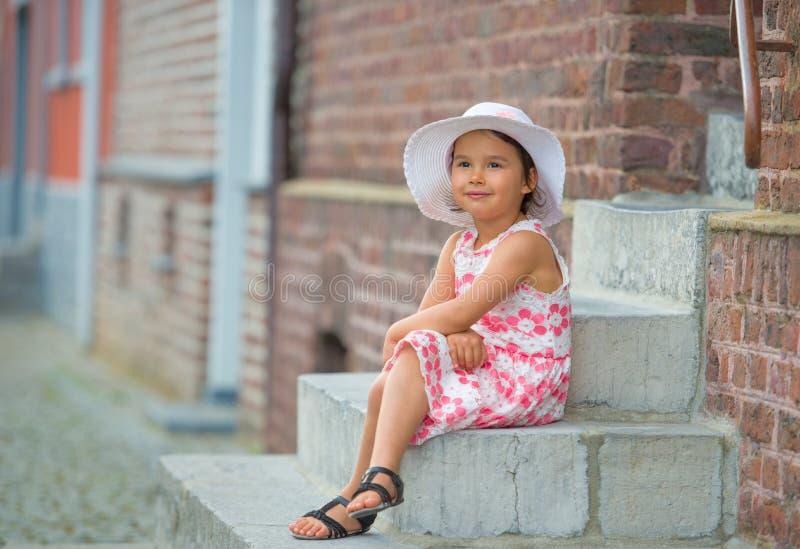 小女孩佩带的白色帽子坐台阶在温暖和晴朗的夏日 库存图片