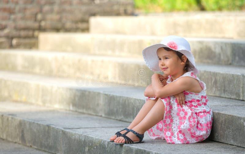 小女孩佩带的白色帽子坐台阶在温暖和晴朗的夏日 图库摄影