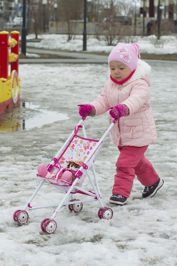 小女孩使用与一辆玩具婴儿车在冬天在 库存图片