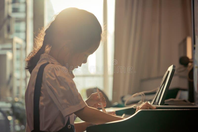 小女孩使用与钢琴的和音乐在家压片 库存图片