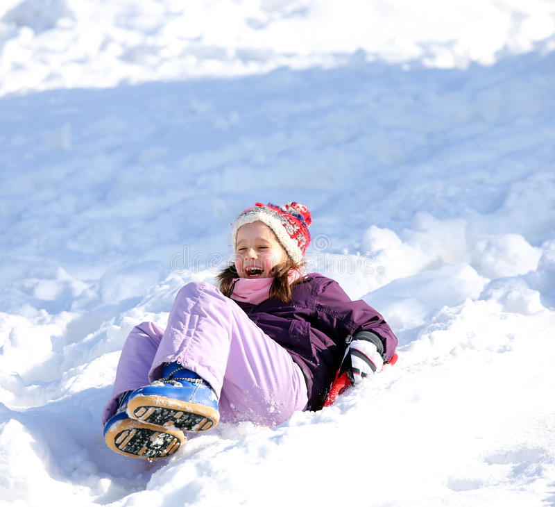 小女孩使用与sledding在雪在冬天 图库摄影