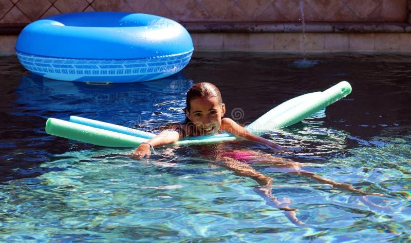 小女孩使用在水池的嫉妒孩子在热带手段在Los Cabos墨西哥 免版税库存照片