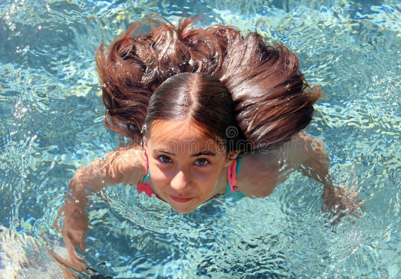 小女孩使用在水池的嫉妒孩子在热带手段在Los Cabos墨西哥 免版税图库摄影