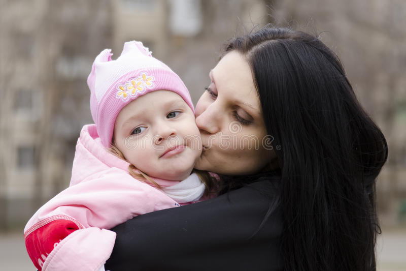 妈妈亲吻了他的手的小女孩 免版税图库摄影