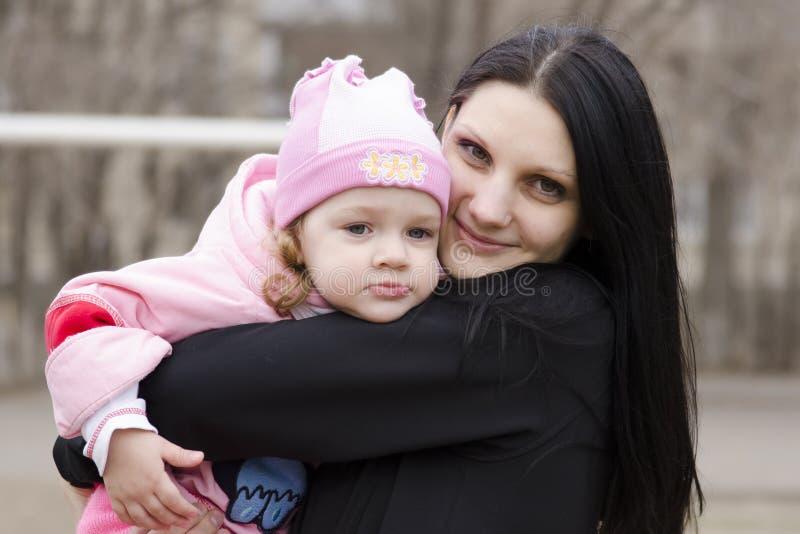 小女孩在我的母亲肩膀周道地说谎  免版税库存照片