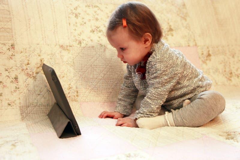小女孩凝视片剂 免版税库存照片