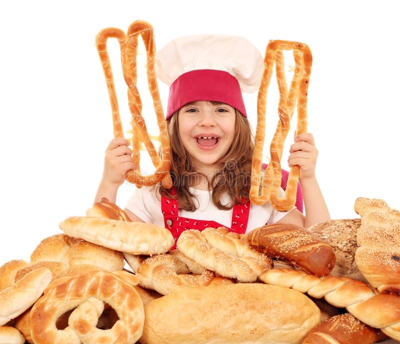 小女孩厨师用另外面包小圆面包和卷 免版税库存图片