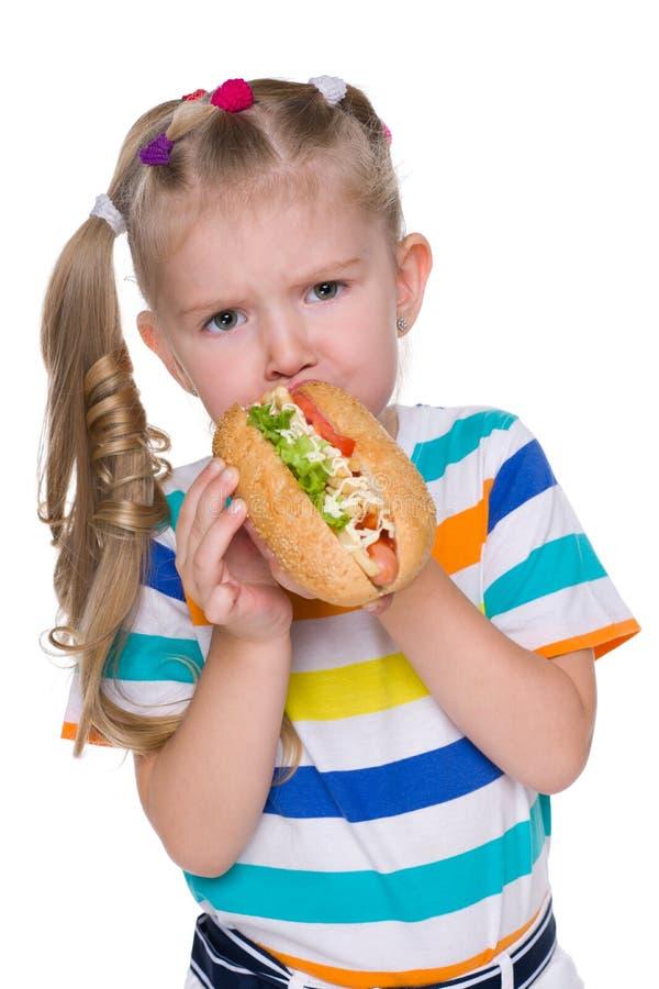 小女孩吃热狗 免版税库存照片