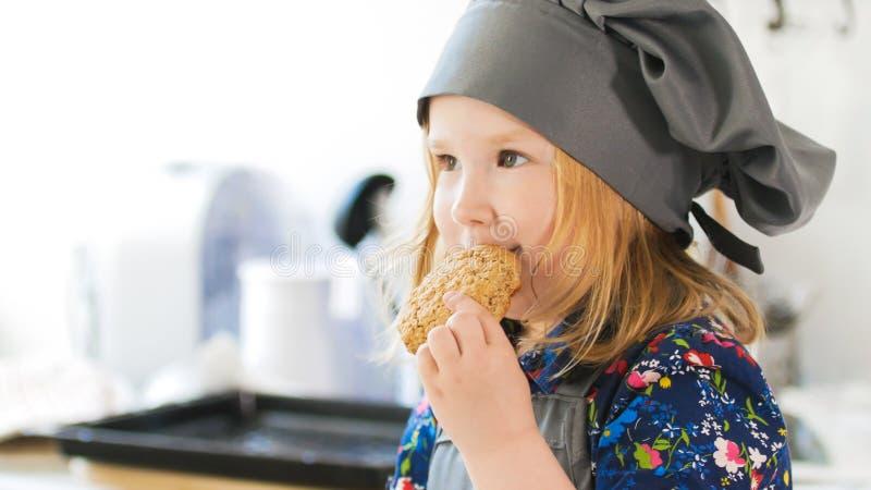 小女孩吃自创曲奇饼用果酱准备着用他们自己的手 免版税库存照片
