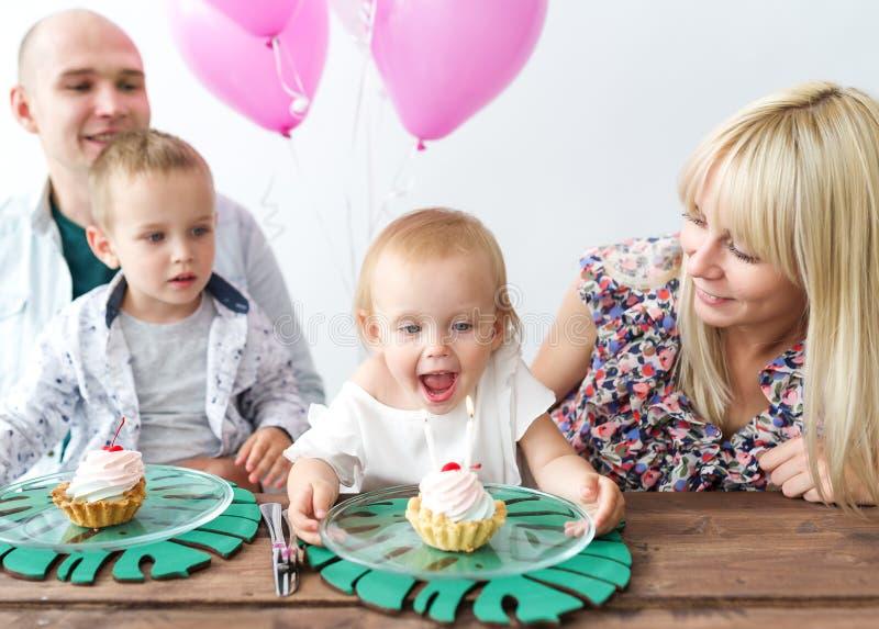 小女孩吹灭蜡烛 庆祝女儿的一个生日聚会生日的愉快的家庭 免版税库存照片