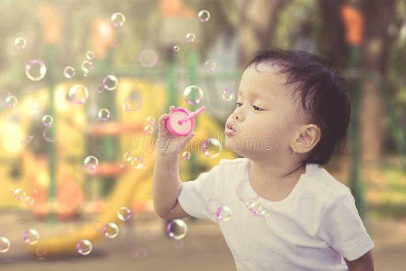 小女孩吹的肥皂泡在操场 免版税库存照片