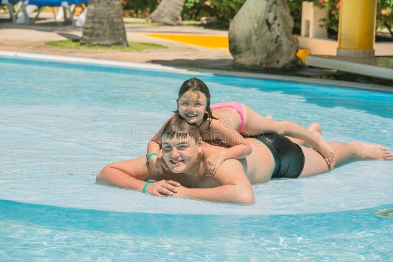 小女孩和十几岁的男孩获得乐趣在庭院游泳池在晴朗的温暖的天 库存图片