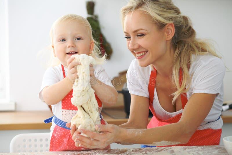 小女孩和她白肤金发的妈妈笑红色的围裙的使用和,当揉面团在厨房里时 Homemad 免版税图库摄影