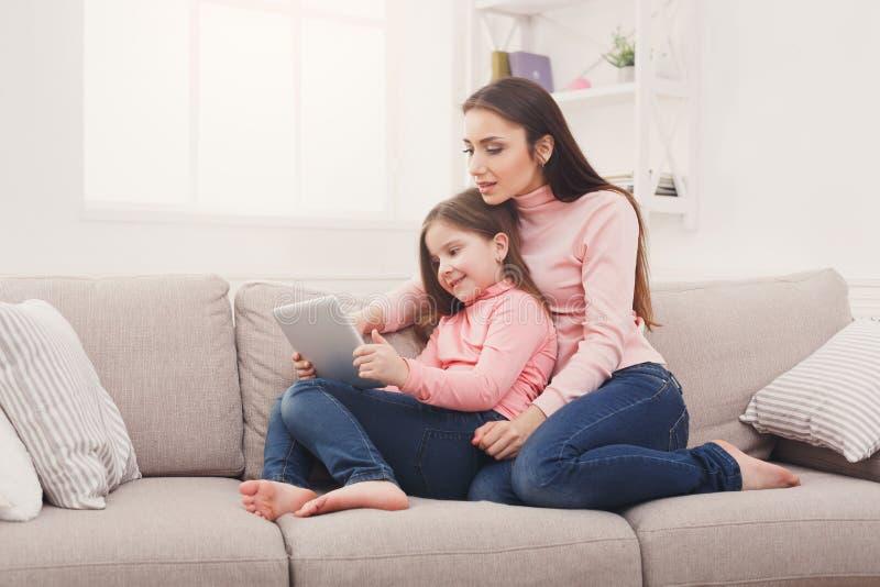 小女孩和她的在家使用片剂的妈妈 免版税库存照片