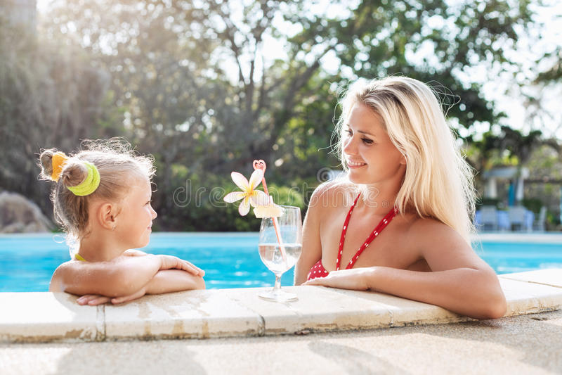 小女孩和她的母亲有鸡尾酒的在热带海滩水池 免版税库存图片