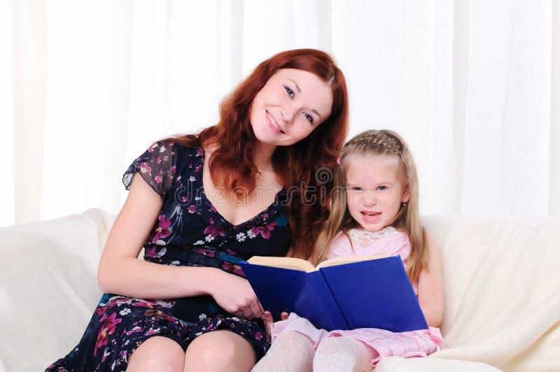 小女孩和她的母亲读了一本书 免版税库存图片