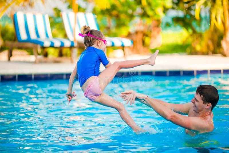 小女孩和愉快的父亲获得乐趣在户外游泳池 库存照片