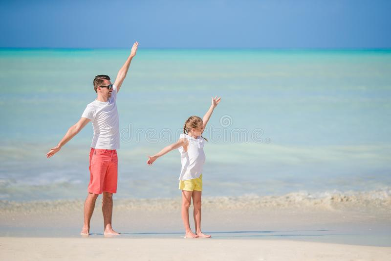 小女孩和愉快的爸爸获得乐趣在海滩假期时 图库摄影