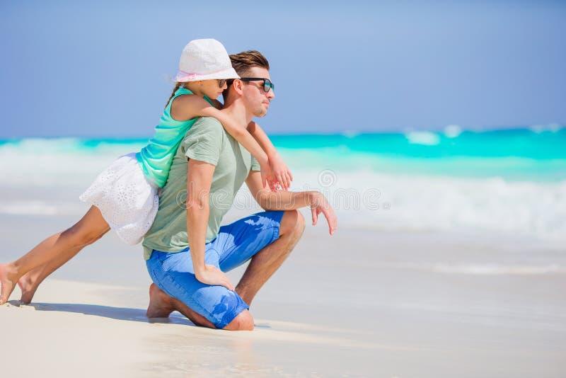 小女孩和愉快的爸爸获得乐趣在海滩假期时 免版税库存图片