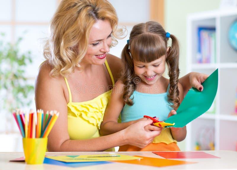 小女孩和母亲与剪刀的切口纸 免版税图库摄影
