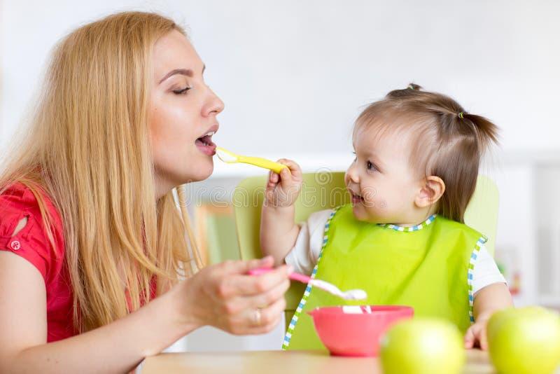 小女孩和母亲用喂养的婴儿食品,坐在桌上在托儿所 免版税图库摄影
