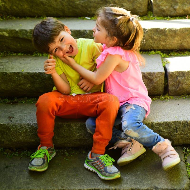 小女孩和男孩台阶的 关系 童年首先爱 小孩夫妇  男孩和女孩 使布赖顿椅子日甲板英国节假日懒人海边有风夏天的星期日靠岸 免版税库存照片
