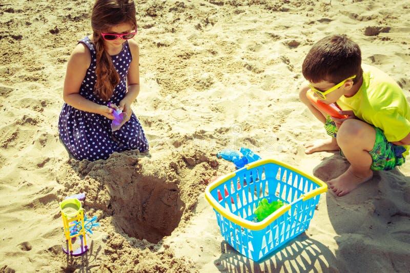 小女孩和男孩有铁锹的获得乐趣在海滩 库存照片