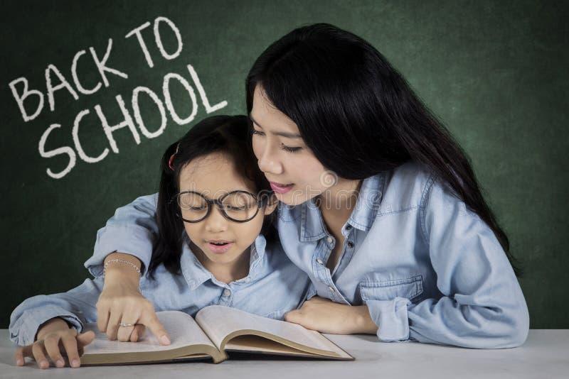 小女孩和老师读了一本书 免版税库存照片