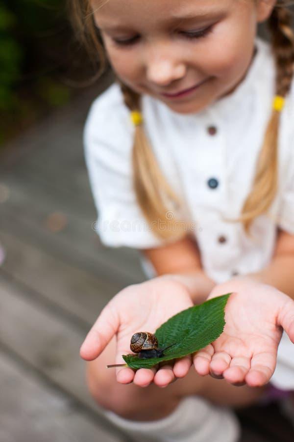 小女孩和蜗牛 库存照片