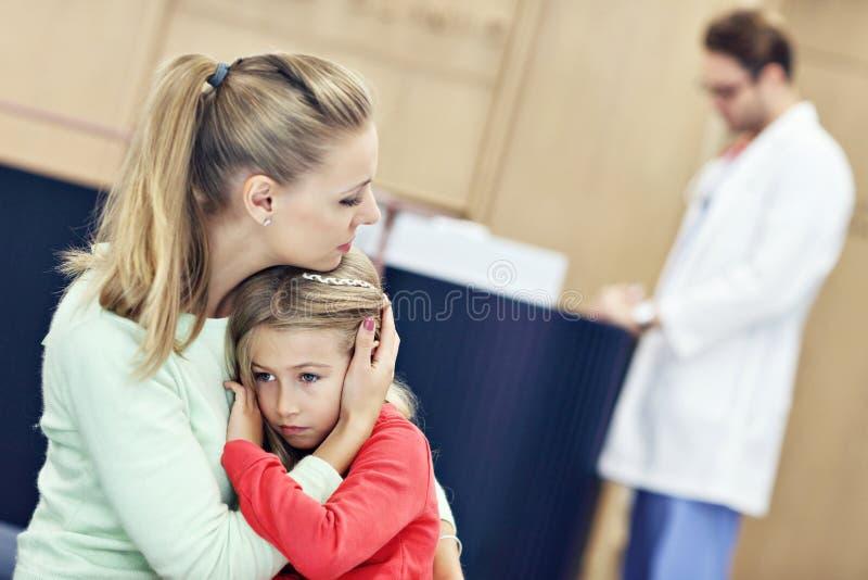 小女孩哭泣,当与她的母亲在咨询的时一位医生 库存图片